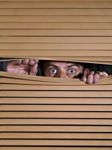 Man spying on something through venetian blinds